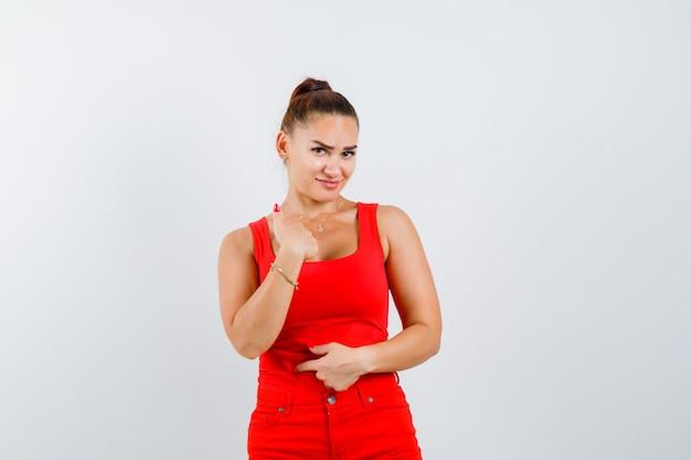 Jonge vrouw wijzend op zichzelf in rood mouwloos onderhemd, broek en nieuwsgierig, vooraanzicht kijkt.