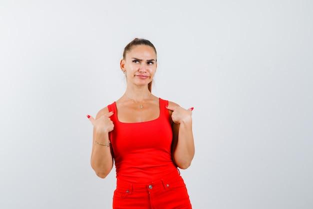 Jonge vrouw wijzend op zichzelf in rood mouwloos onderhemd, broek en op zoek ontevreden, vooraanzicht.