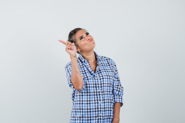 Jonge vrouw wijzend opzij terwijl opgeblazen haar wangen in geruit overhemd