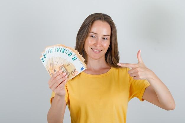 Jonge vrouw wijzende vinger naar eurobankbiljetten in geel t-shirt en op zoek gelukkig