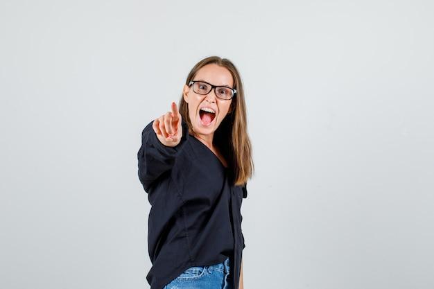 Jonge vrouw wijzende vinger op camera in shirt, korte broek, bril en energiek kijken