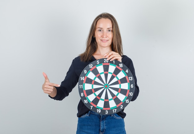 Jonge vrouw wijzende vinger op dartbord in zwart shirt, jeans broek en op zoek vrolijk