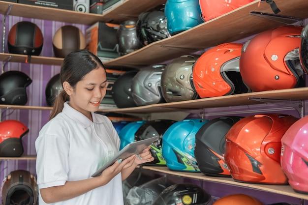 Jonge vrouw winkelbediende permanent met behulp van een digitale tablet in de helmwinkel