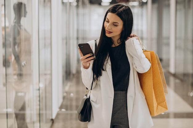 Jonge vrouw winkelen bij winkelcentrum