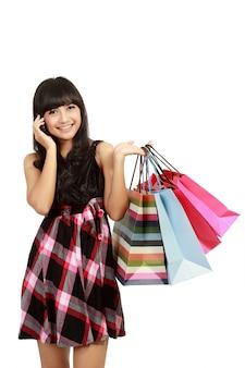 Jonge vrouw winkelen en haar vrienden bellen