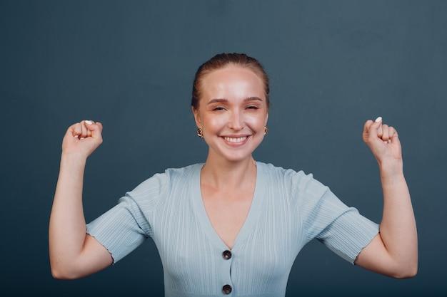 Jonge vrouw winnaar vreugde en gooit zijn handen omhoog opgeheven armen in de lucht