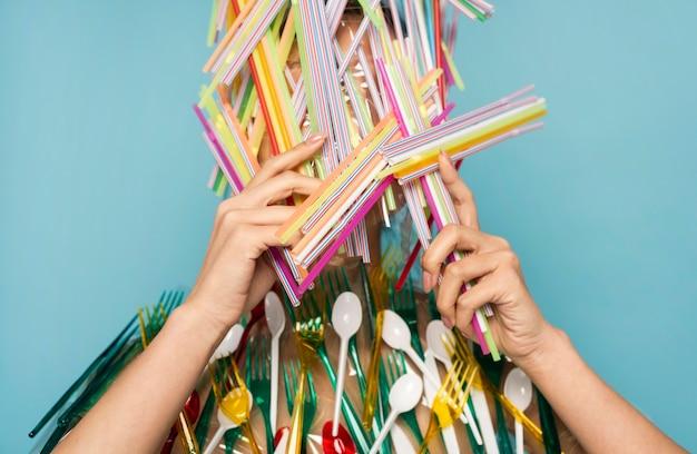 Jonge vrouw wordt bedekt met kleurrijke plastic rietjes en tafelgerei