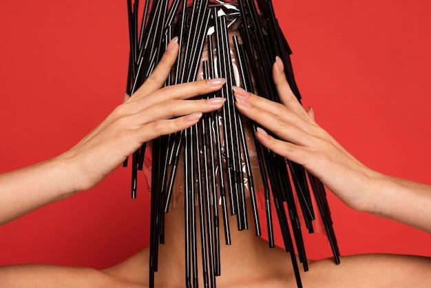 Jonge vrouw wordt bedekt met plastic zwarte rietjes