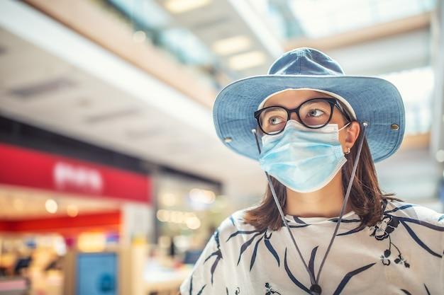 Jonge vrouw wordt beschermd tegen coronavirus met een beschermend masker in het interieur van de supermarkt.