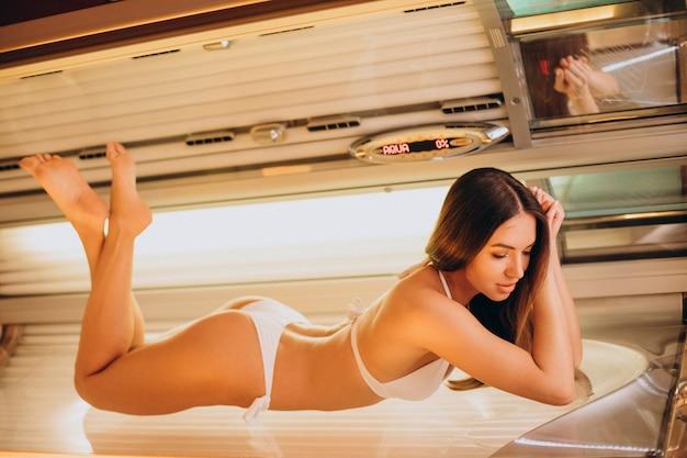 Jonge vrouw wordt bruin in het solarium