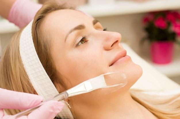 Jonge vrouw wordt met een borstel op het masker op het gezicht aangebracht. procedure bij de schoonheidsspecialist.