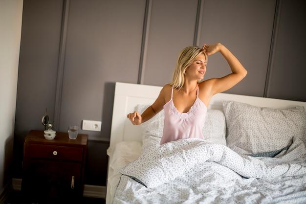 Jonge vrouw wordt wakker in de ochtend