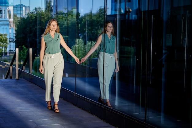 Jonge vrouw wordt weerspiegeld in het glas van een kantoorgebouw terwijl ze naar buiten loopt in een sexy pak
