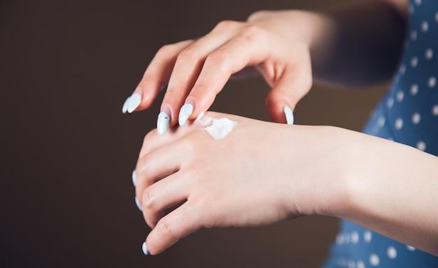 Jonge vrouw wrijft haar hand in met crème