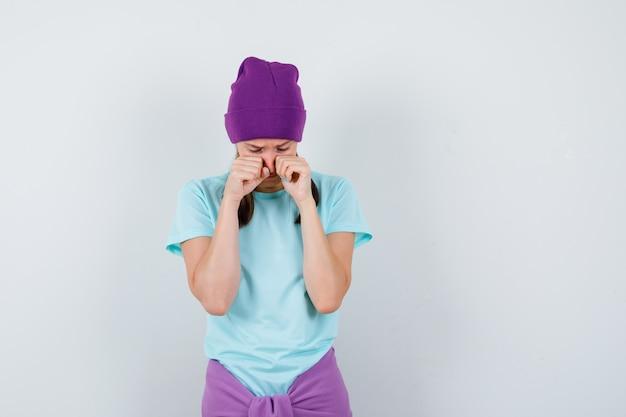 Jonge vrouw wrijft in de ogen met handen terwijl ze huilt in blauw t-shirt, paarse muts en ziet er verdrietig uit. vooraanzicht.