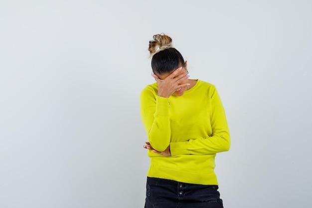 Jonge vrouw wrijft voorhoofd in trui, spijkerrok en ziet er uitgeput uit
