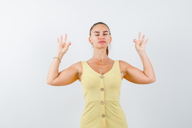 Jonge vrouw yoga gebaar met gesloten ogen in gele jurk tonen en op zoek ontspannen. vooraanzicht.