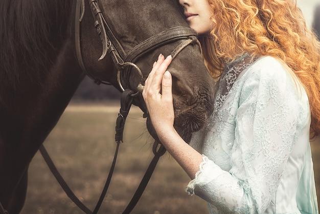 Jonge vrouw, zachtjes knuffelend een paard, streelde zijn hoofd.