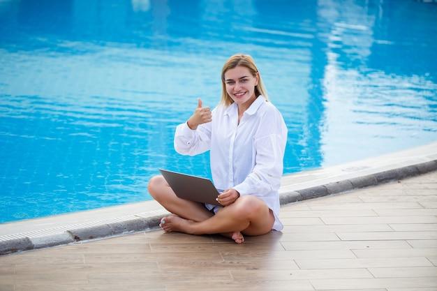 Jonge vrouw zakenman met laptop zitten bij het zwembad. open werkplek. freelancer-concept. online winkelen. vakantiewerk