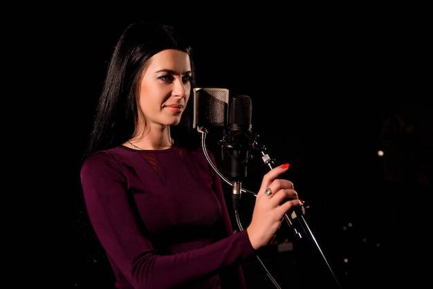 Jonge vrouw zanger voor microfoon.