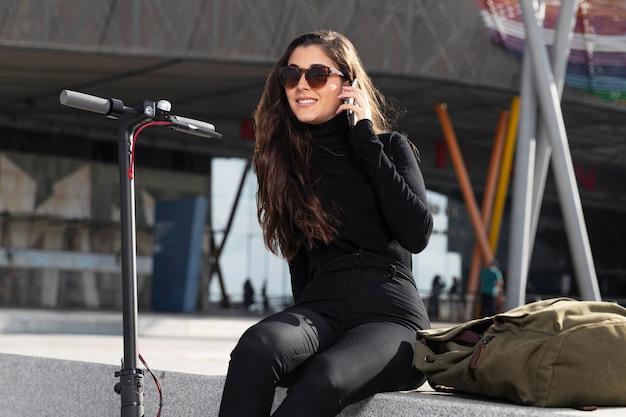 Jonge vrouw zat naast haar scooter