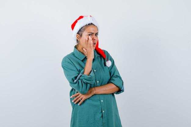 Jonge vrouw zegt geheim door hand in de buurt van mond in shirt, kerstmuts te houden en voorzichtig te kijken, vooraanzicht.