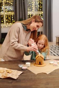 Jonge vrouw zelfgemaakte peperkoek huis versieren met slagroom terwijl haar schattige kleine daghter in de buurt staan en ernaar kijken