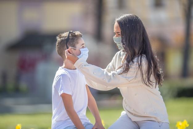 Jonge vrouw zet een gezichtsmasker op een jeugdmannetje op een zonnige dag in de stad.