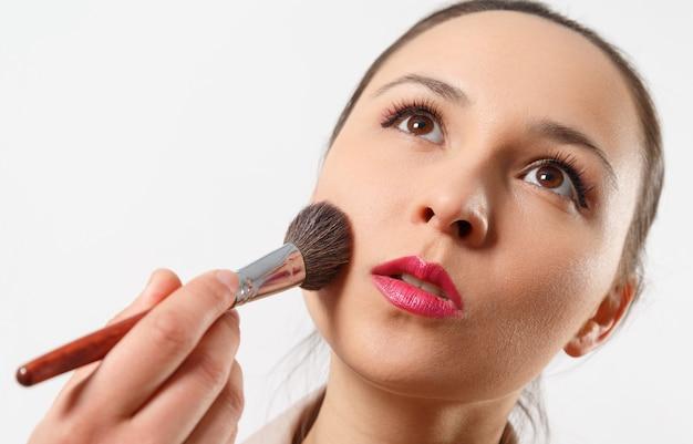 Jonge vrouw zet make-up op haar gezicht met een penseel op wit
