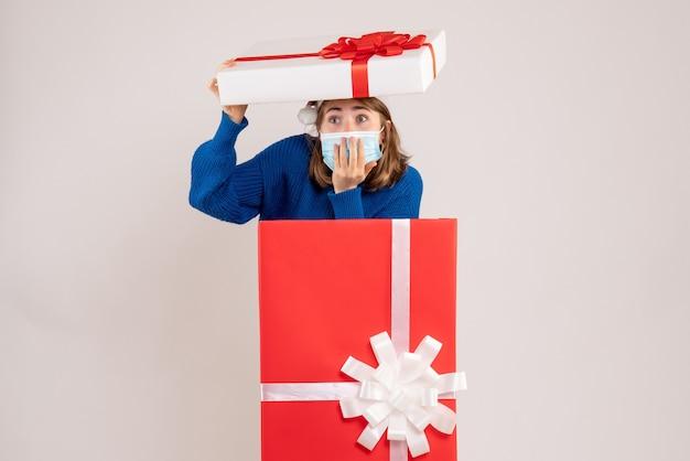 Jonge vrouw zichzelf verbergen in huidige doos met verbaasd gezicht op wit