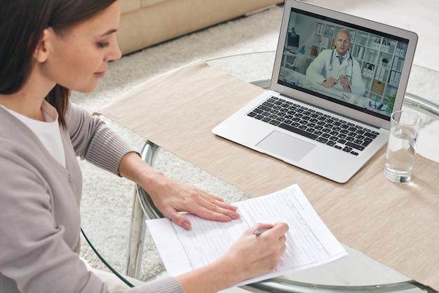 Jonge vrouw ziekteverzekering formulier invullen en kijken naar online video waar arts medisch advies geeft