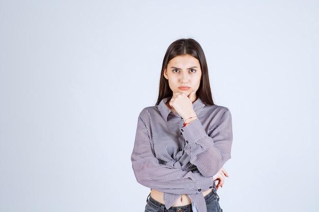 Jonge vrouw ziet er bedachtzaam en brainstormend uit