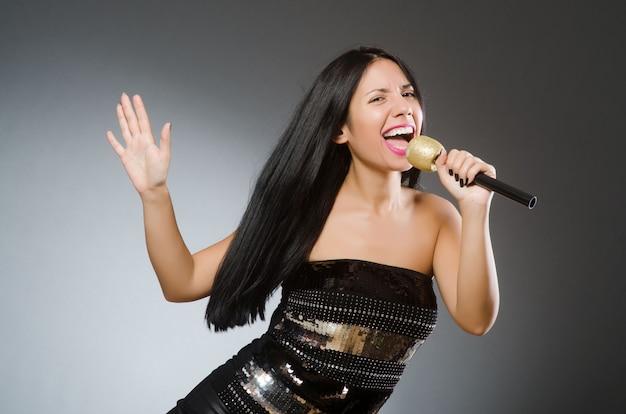 Jonge vrouw zingen in karaoke-club