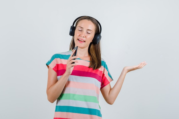 Jonge vrouw zingen in mobiele telefoon als microfoon in t-shirt, koptelefoon, vooraanzicht.