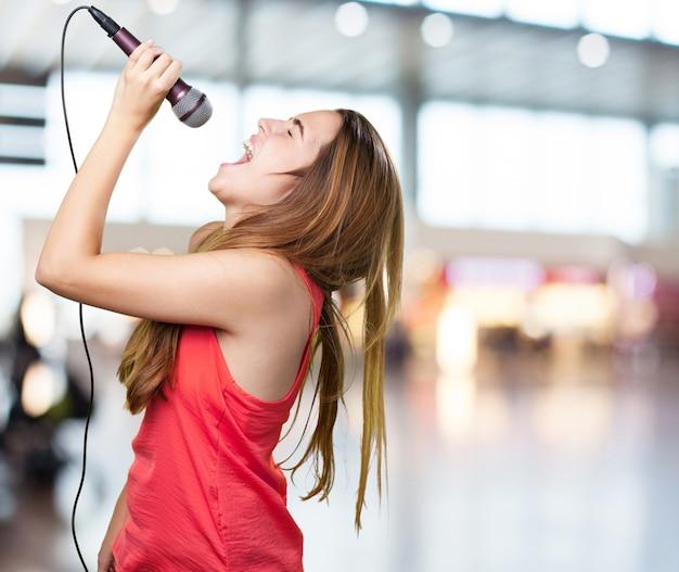 Jonge vrouw zingen met een microfoon op een witte achtergrond