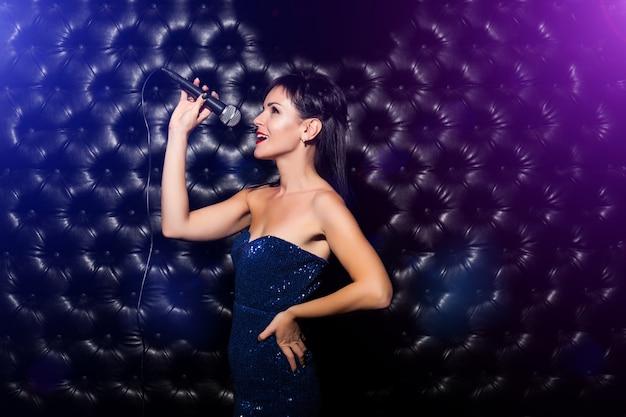 Jonge vrouw zingen met microfoon tegen donker