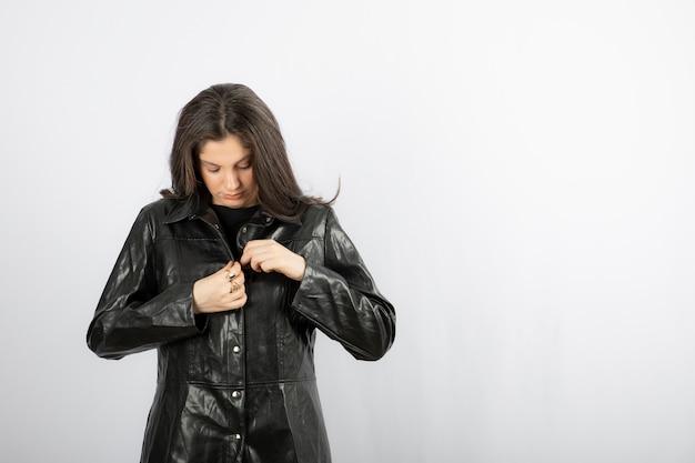 Jonge vrouw zippen zwarte jas.