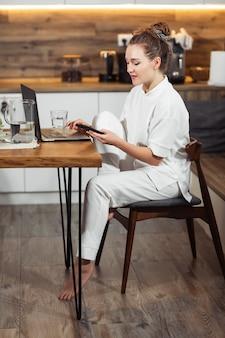 Jonge vrouw zit aan de keukentafel met behulp van een laptop en praten op een mobiele telefoon en glimlachen. succesvol en meisje dat thuis lacht werkt. mooie modieuze en vrouw die thuis glimlachen ontspannen.