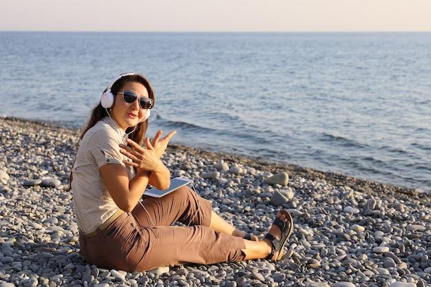 Jonge vrouw zit aan de kust, beweegt handgebaren op het ritme van de muziek
