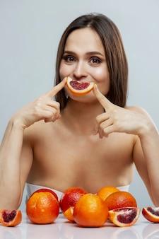Jonge vrouw zit aan een tafel met sinaasappels. mooie brunette in lingerie. gezond eten en vegetarisme.