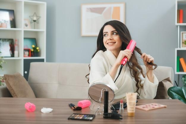 Jonge vrouw zit aan tafel met make-up tools in de woonkamer