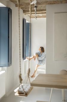 Jonge vrouw zit alleen bij het raam in een lichte kamer thuis. zelfisolatie, eenzaamheid, meisje voelt zich thuis kalm en ontspannen