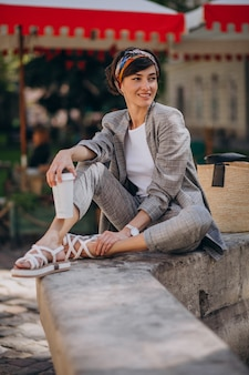 Jonge vrouw zit bij de fontein en drinkt koffie