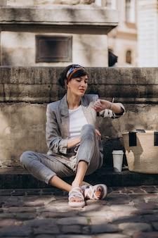Jonge vrouw zit bij de fontein