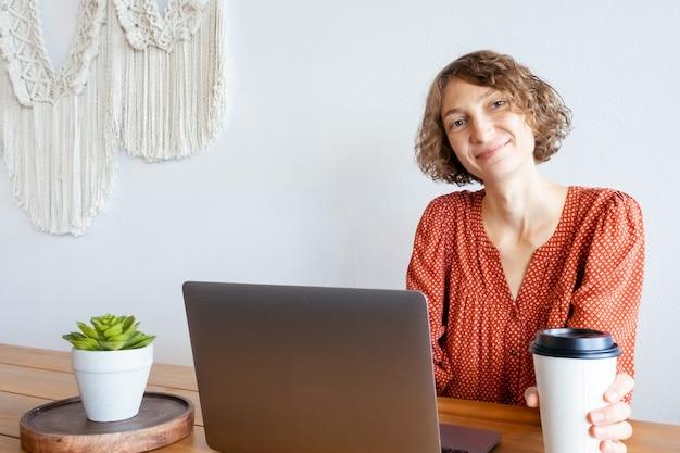Jonge vrouw zit bij de grote ramen van een koffieshop met laptop.