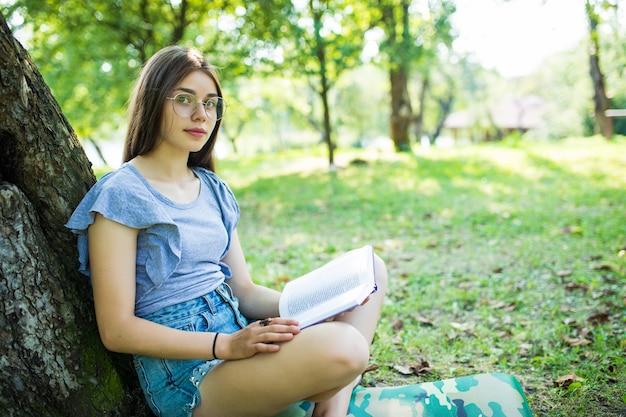 Jonge vrouw zit en leest haar favoriete boek over oa groen gras onder de boom in een mooie zonnige zomer