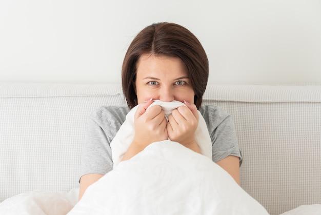 Jonge vrouw zit in bed en is bang en doodsbang