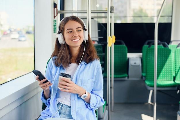 Jonge vrouw zit in de moderne stadsbus, luistert naar muziek, drinkt koffie en kijkt uit het raam.