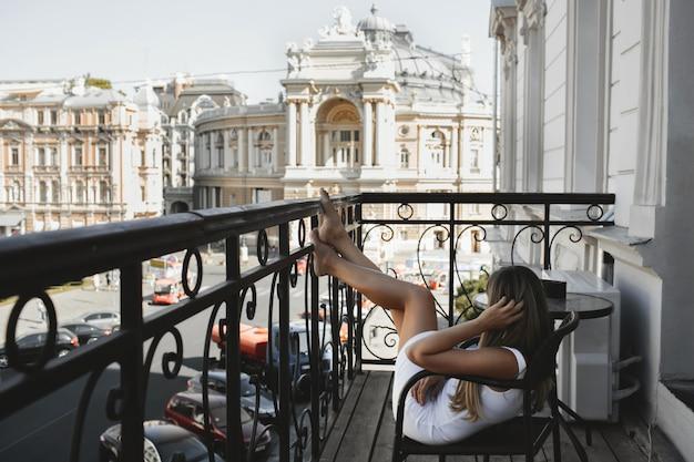 Jonge vrouw zit in de stoel op het balkon op de zonnige dag met prachtige monumentale gebouwen met poten op de metalen leuning