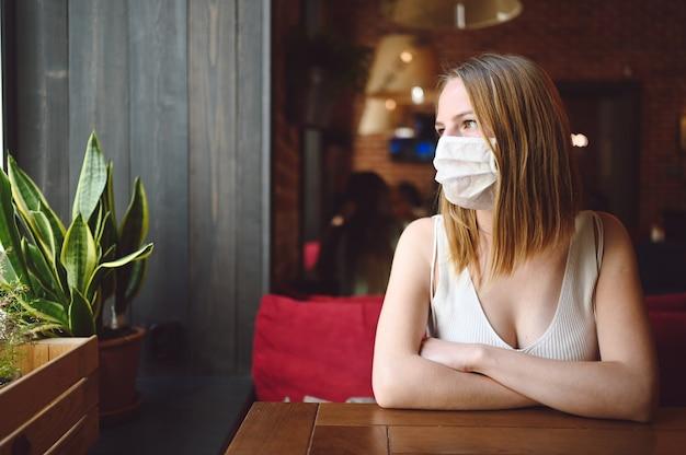 Jonge vrouw zit in een café of restaurant en wacht op haar bestelling met een beschermend gezichtsmasker voor griepviruspreventie.